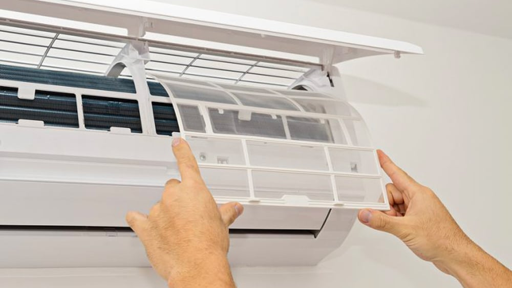An air conditioning repairman servicing an air conditioner in Wollongong