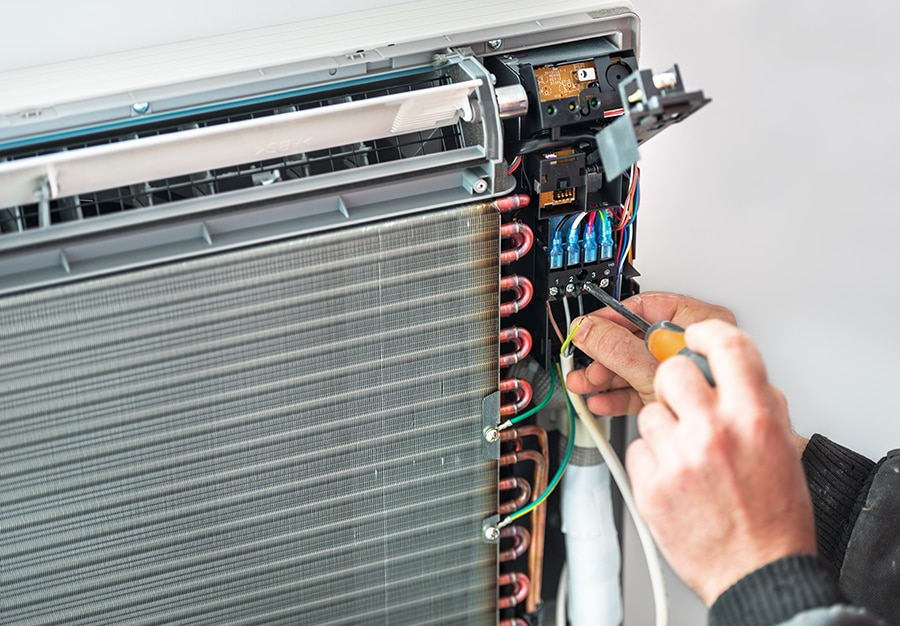 An air conditioner repairman fixing an air conditioner in Wollongong